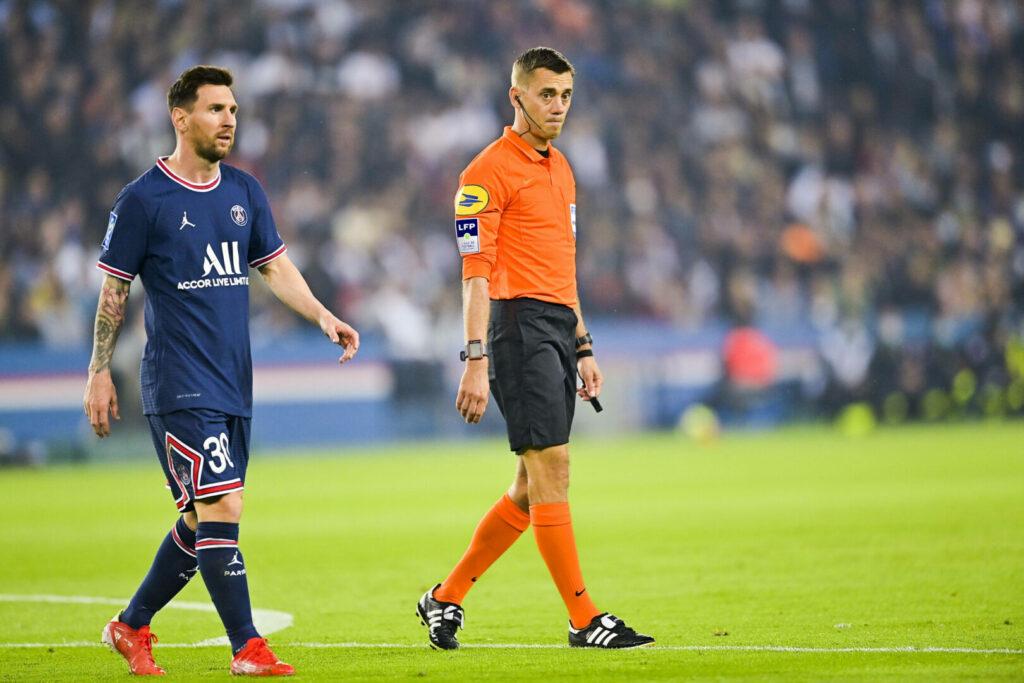 Lionel Messi läuft neben einem Schiedsrichter