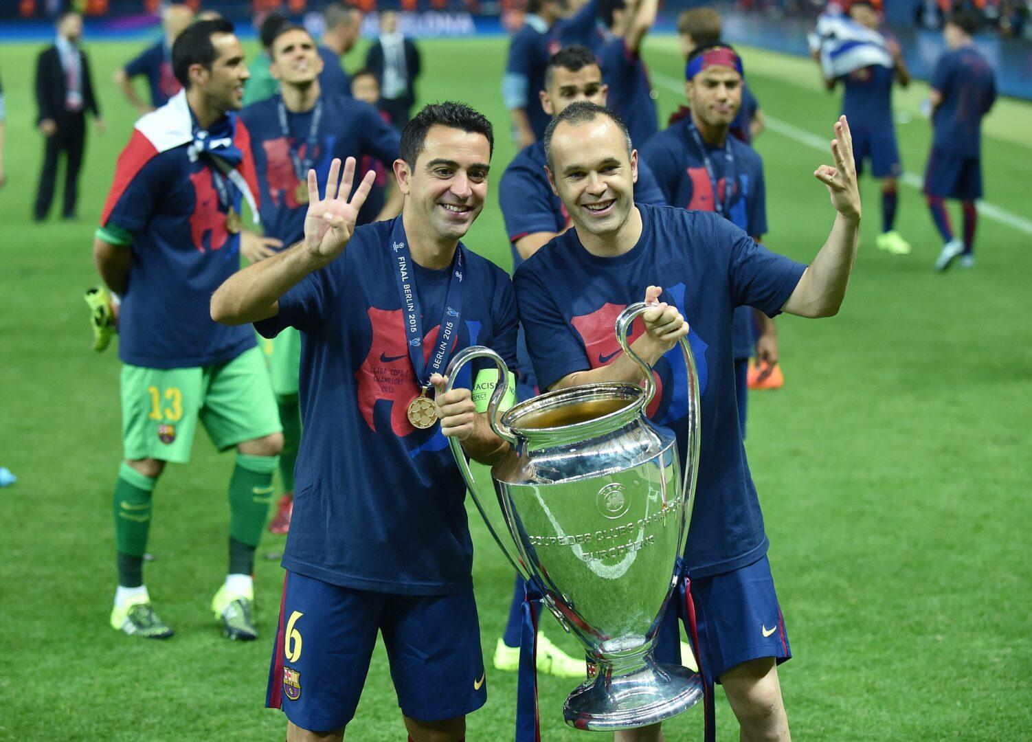 Andres Iniesta und Xavi halten gemeinsam die Trophäe und bejubeln den Gewinn der Champions League 2015