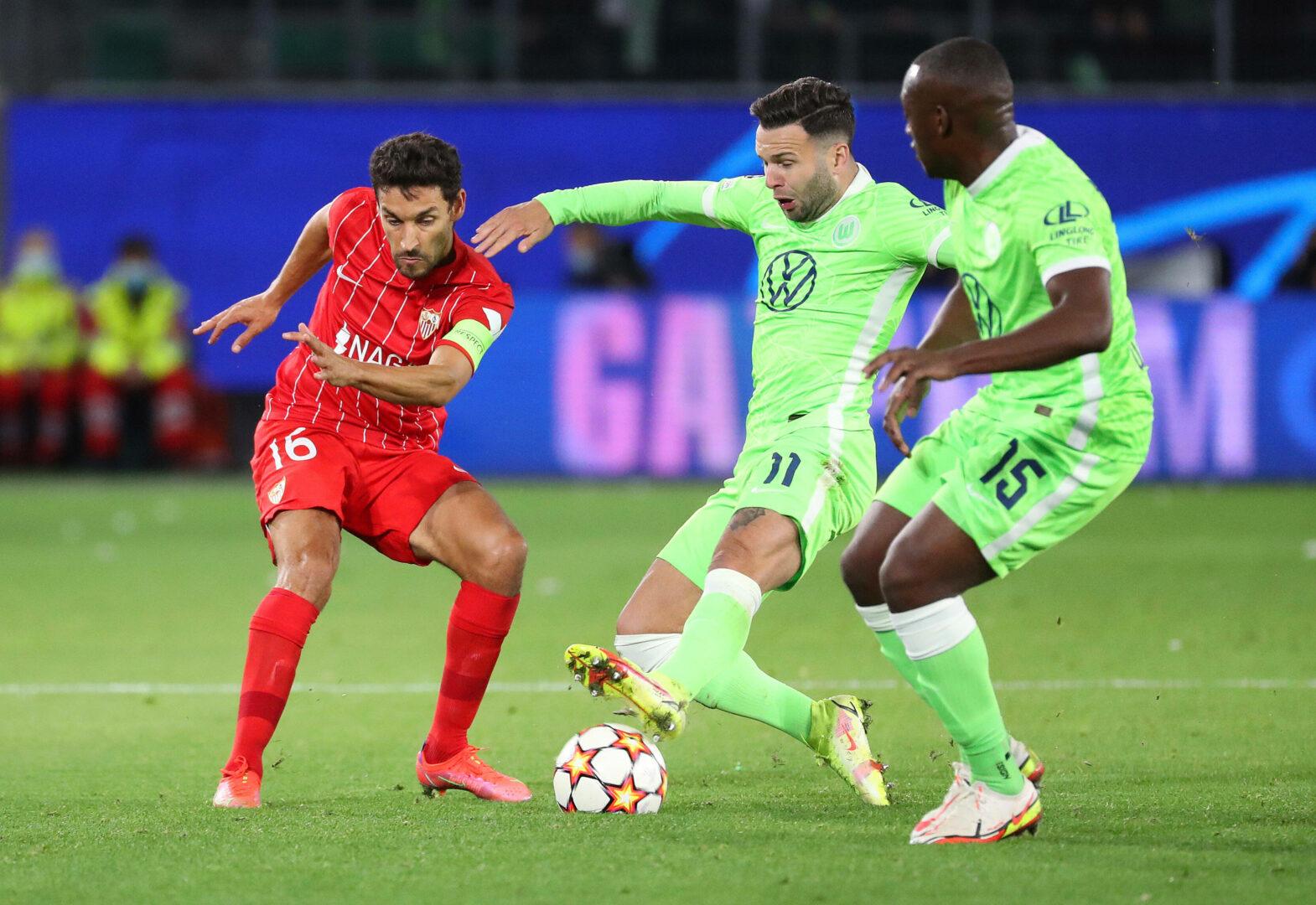 Jesus Navas vom FC Sevilla im Duell mit Renato Steffen und Jerome Roussillon vom VfL Wolfsburg