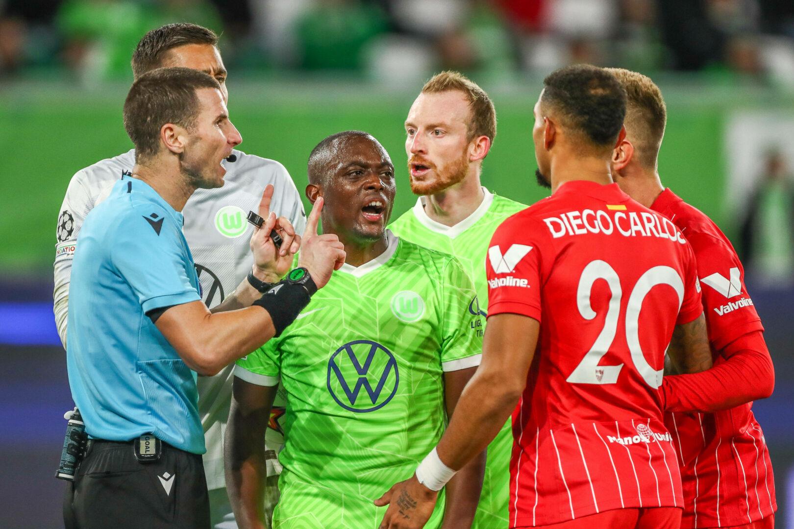Kabakov (Schiedsrichter), Roussilon, Arnold (beide Wolfsburg), Diego Carlos (Sevilla) im Clinch